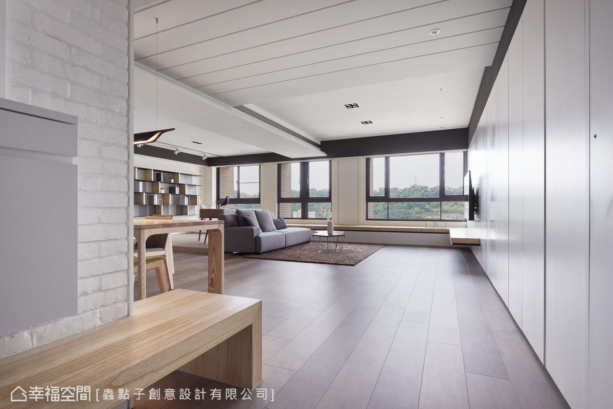 以白色搭配木皮鋪陳空間,凸顯窗外絕佳視野;玄關文化石牆下方延展出穿鞋椅,讓空間機能更為完整。