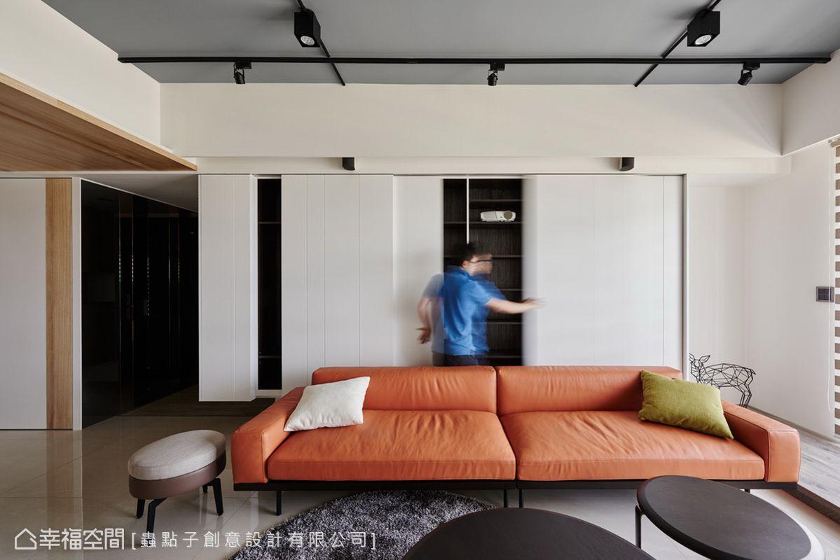 沙發背牆規劃整面懸空收納櫃,白色烤漆門片呈現不規則分割造型,除了隱藏投影機遮蔽機能,也降低立面壓迫感。刻意挑選橘紅色皮件沙發,搭配青綠色抱枕軟件,以活潑跳色手法展現北歐風格。