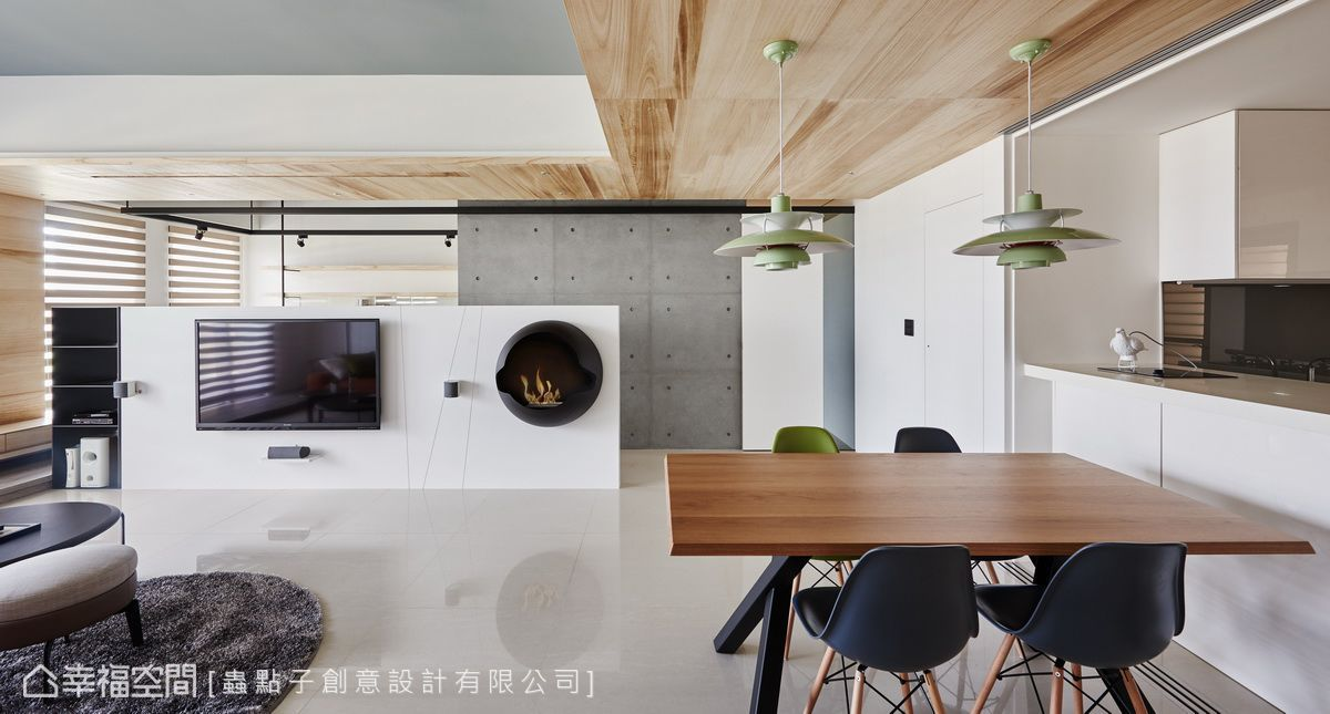當玻璃拉門開啟後,餐桌彷彿與中島相連,形成餐廚合一的配置設計。在開放的格局規劃下,將清水模、鐵件、木皮混合搭配,展現一貫風格手法,創造出前後堆疊的端景層次。