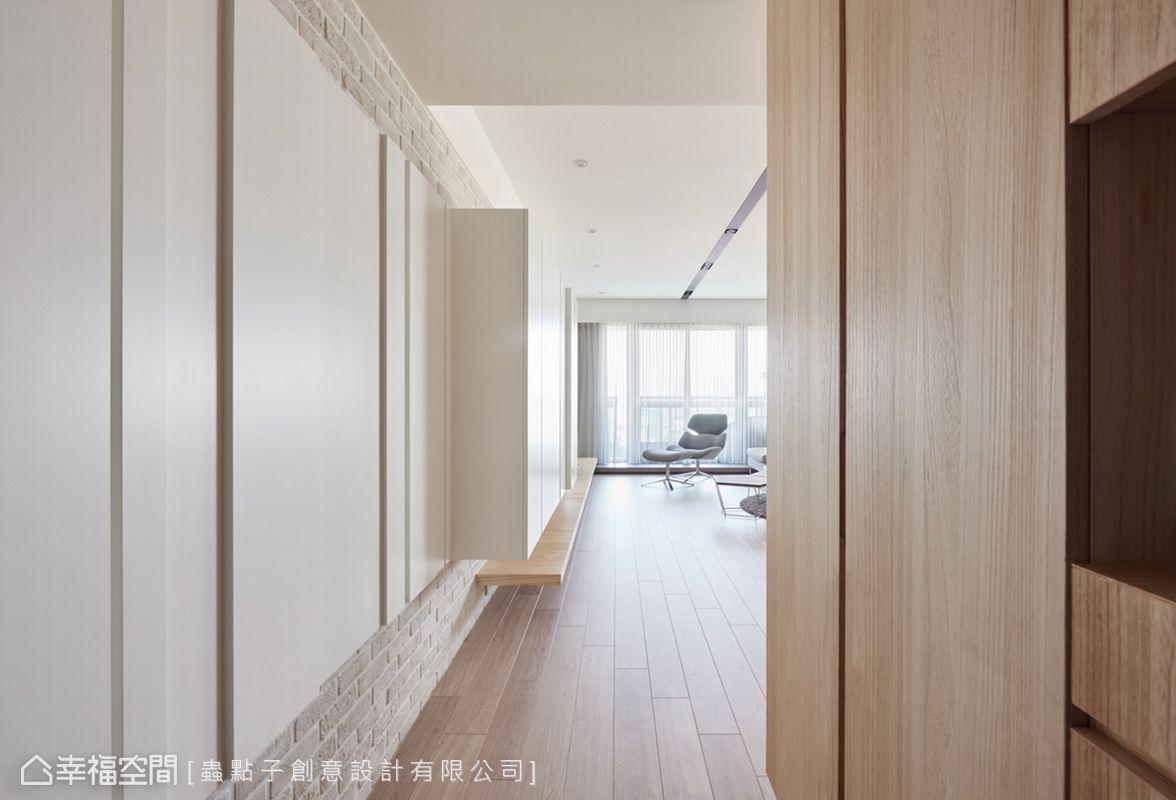 L形收納櫃自玄關轉折進入室內,裡頭藏有一間儲藏室;白色壁板呈現出凹凸立體層次,藉由連續性造型帶來視覺延伸。