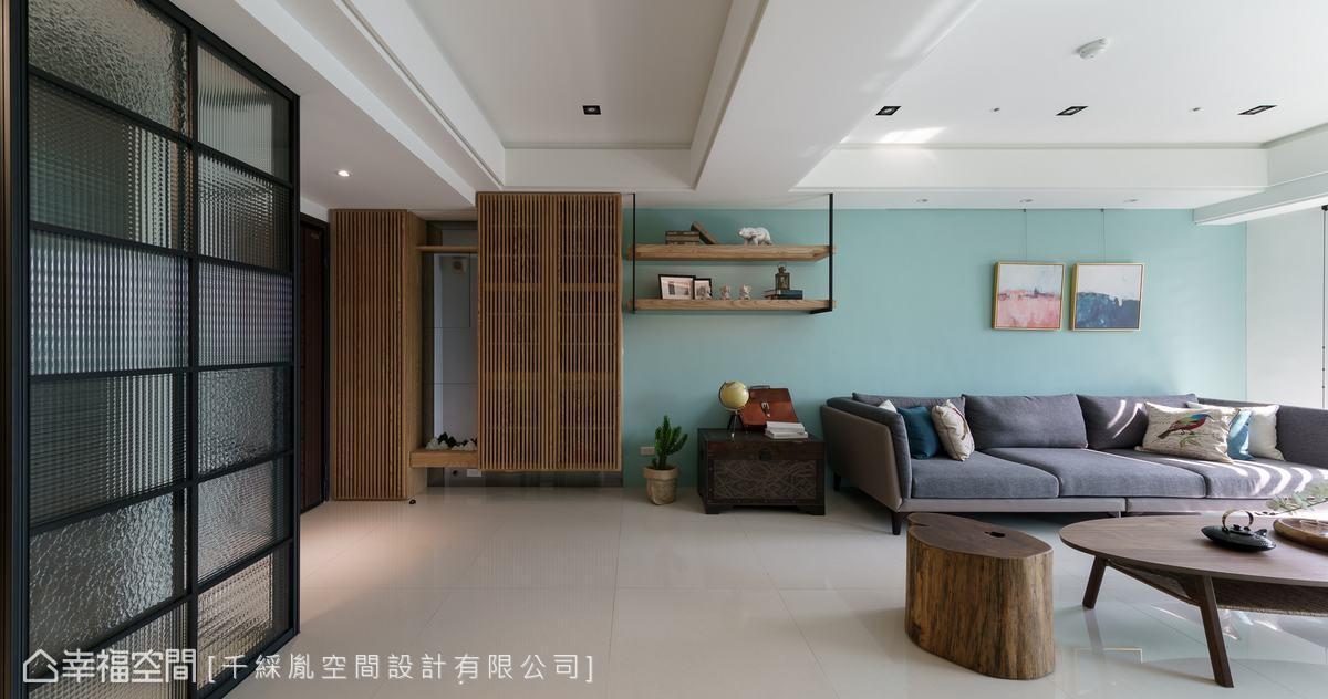 開放式玄關,使視野穿透客廳,搭配整面藍綠色沙發背牆設計,空間更顯寬廣。而結合吊衣櫃及鞋櫃的設計,滿足屋主的收納需求。
