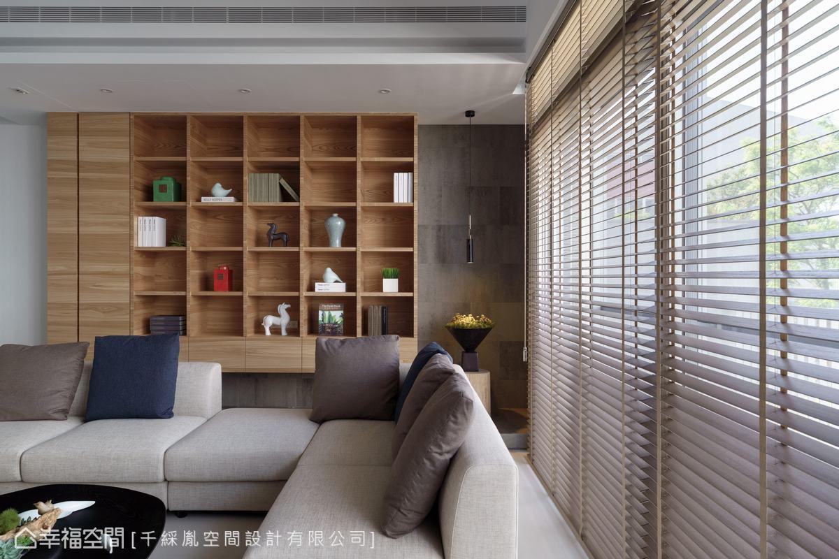 運用懸吊木作展示櫃做為沙發背牆,可以視屋主的喜好或收藏,而木質百葉可調整光源,帶給空間不同面貌。
