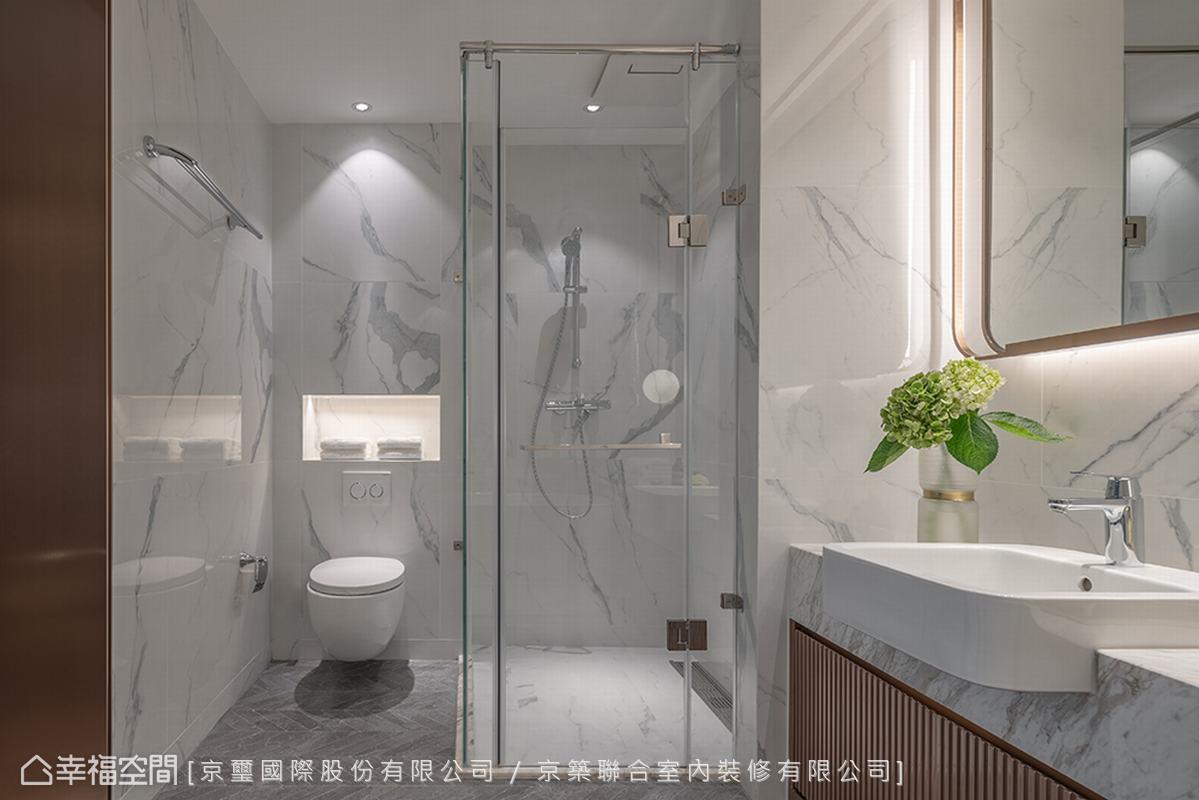 地坪使用灰色魚骨紋理石材,搭配立面大理石紋瓷磚,變化深淺色調,加上與主臥梳妝鏡面呼應的金屬細節,砌築具有當代俐落洗鍊精神的衛浴空間。
