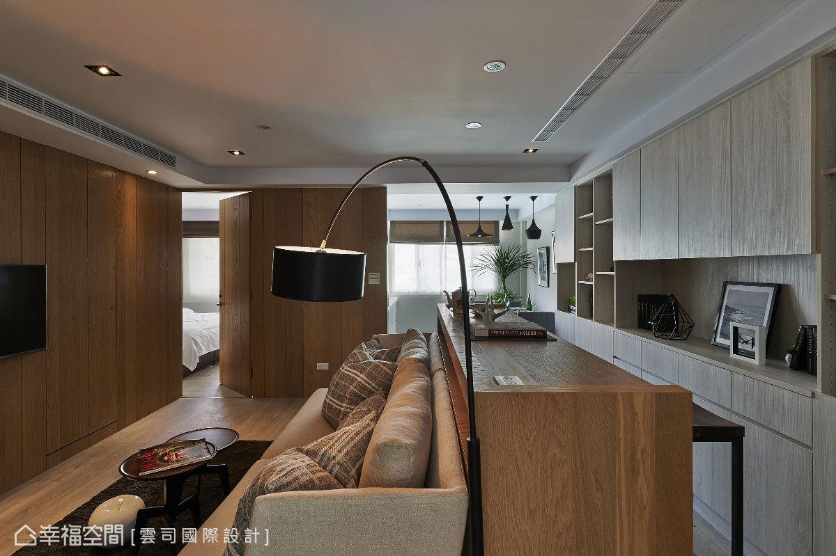 設計款的高背沙發後方,以吧檯式的閱讀機能段落為倚靠,透過使用高度的變化豐富空間的垂直層次。
