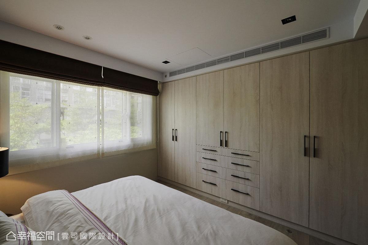 梁下空間利用系統櫃規劃衣物收納,特別挑選的門扇材質與鐵件把手,於空間中十分相襯。