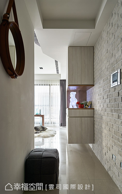 玄關右側的牆面以文化石做鋪陳,端景處的展示櫃設計,不僅化解視線的壓迫感,也成為一處趣味的段落風景。