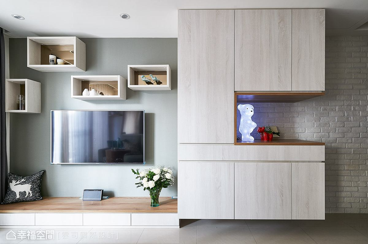 電視主牆以灰綠色日本進口壁紙做鋪陳,電視上方的展示櫃隨興錯落於牆面上,增添活潑的立面表情。