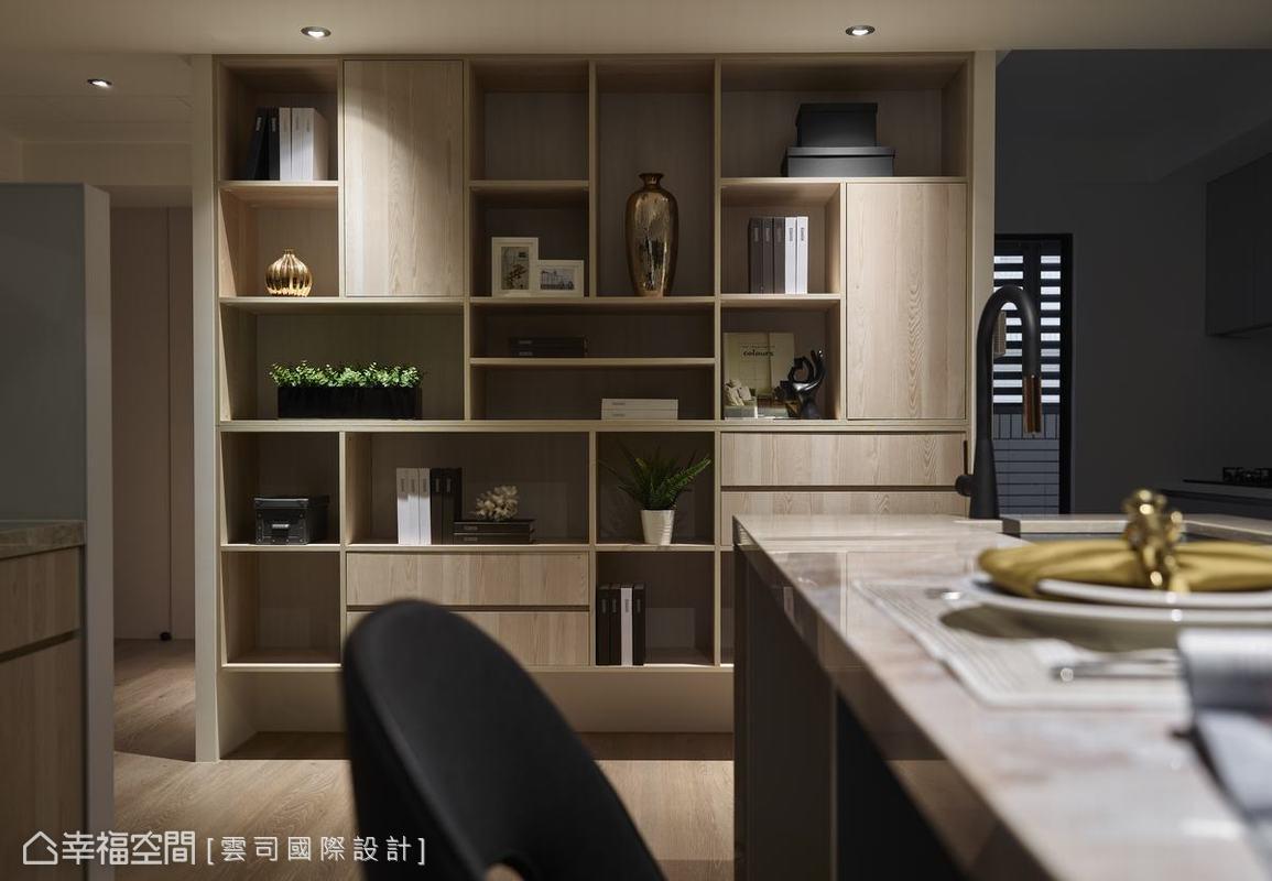 吧台一旁設置結合開放與密閉式收納的大型櫃體,讓裝飾品與生活雜物都有適當的擺放空間,原木語彙與超耐磨地板傳遞閒適的自然氛圍。