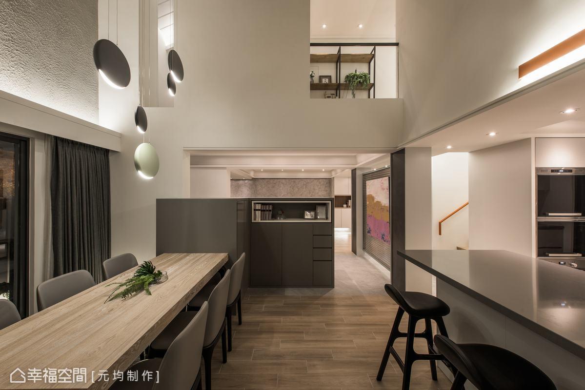 從電視櫃的縱向延伸出餐桌,前方可見女屋主作菜身影,後方則有大片綠景,營造良好用餐氛圍。