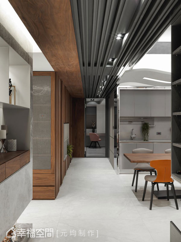走廊道串連起公私領域動線成為空間隱性的動線指引,天花板運用手工格柵讓視線得以往內延伸;結合木皮元素呈現L形轉折設計,讓天壁立面銜接一氣呵成形成連續性的表情層次。