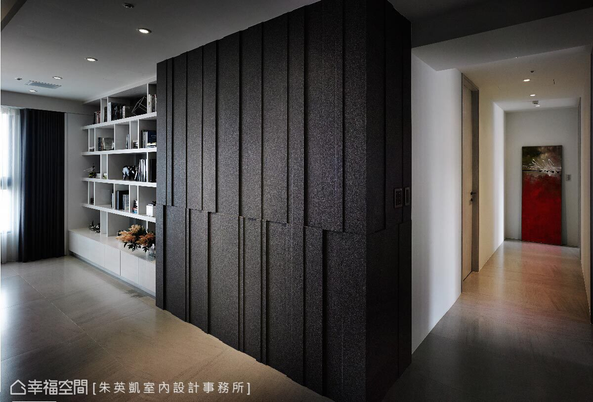 深灰牆體後方為主臥更衣室,受限於樑柱結構,朱英凱設計師利用內縮手法設計出整面書櫃牆。