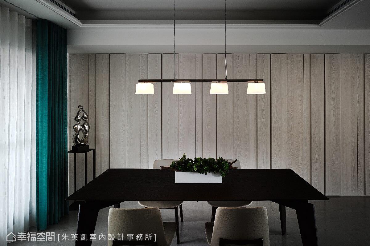 餐桌後方原為消防逃生門,朱英凱設計師利用一整面木紋作為掩蓋,門片的溝縫線條增添空間些許韻律感。