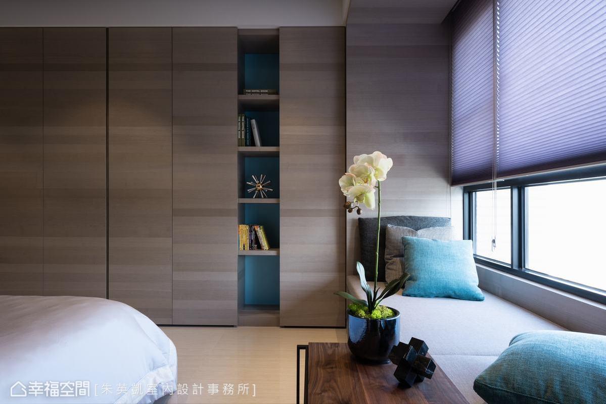 窗邊臥榻是屋主看書放鬆的好所在,且運用下方空間增加收納功能,一旁書櫃與抱枕選用鮮豔藍綠色,增加亮點。