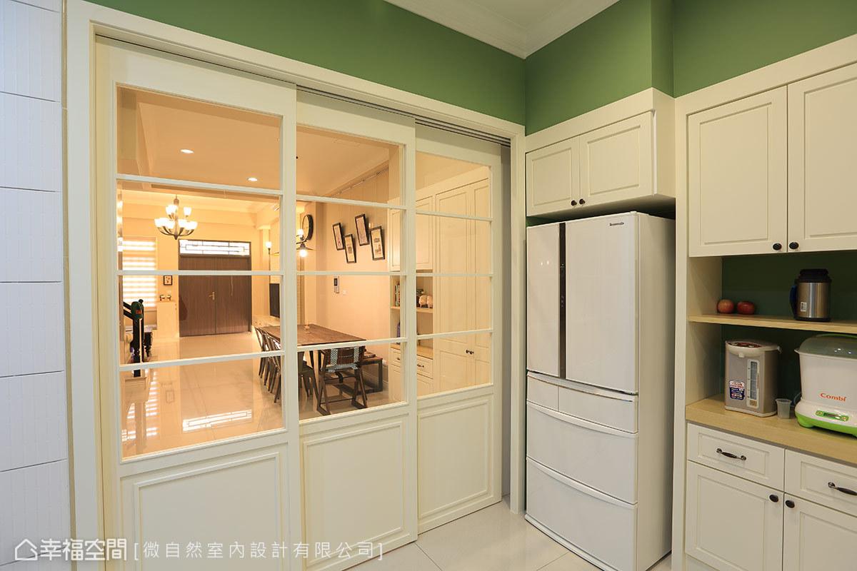 簡單的廚具線條與拉門相呼應,讓美式新古典的風格元素,自然漫入生活的每一個角落。而纖細的線條與玻璃材質,也讓傳統狹長型透天厝的前後採光得以貫連。