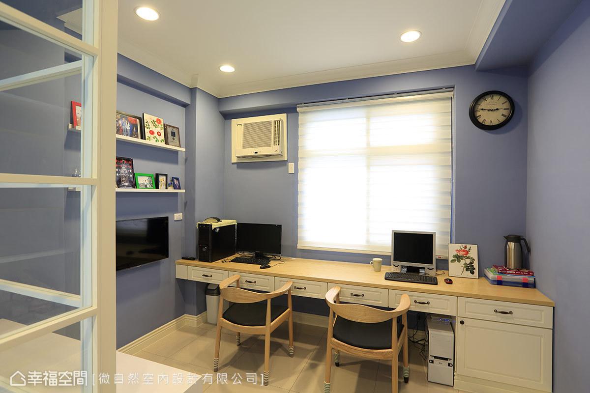 以輕鬆的藍色填滿牆壁,搭配雙人使用的長書桌及牆上展示架,創造實用又不失設計感的書房風格。