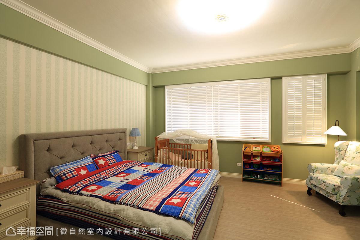 以綠色和條紋壁紙妝點的主臥房,角落擺放一張單椅與立燈,營造美式住家特有的優雅與自在。