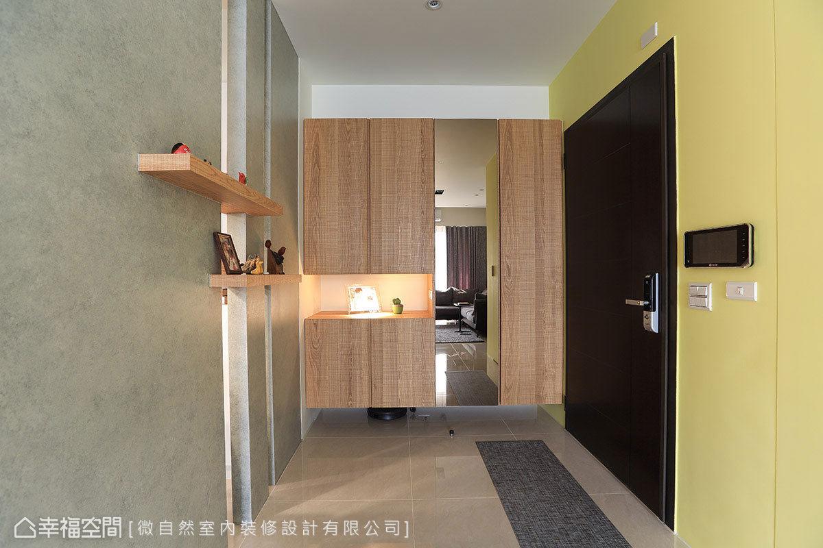 進入玄關,設計師徐以倫替屋主規劃鞋櫃與外出衣帽櫃,以騰空設計營造輕盈感,並能於下方置入掃地機器人。