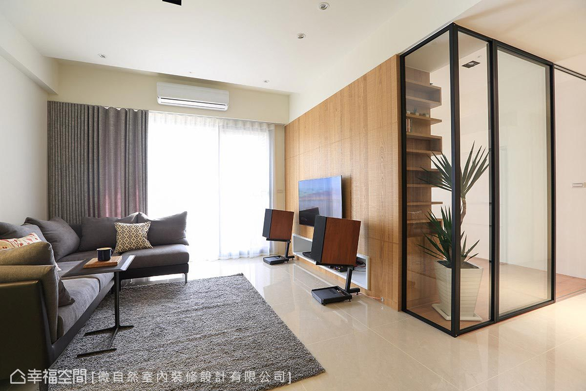 電視牆與書房的轉角處,以清透的玻璃取代實牆,串聯視覺上的軸線與景深,並於書房櫃體規劃展示層板,增添豐富的層次變化。