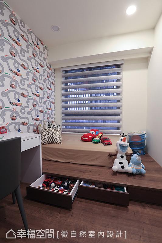 男孩房使用架高木地板替代床架,下方規劃收納抽屜;立面鋪貼賽車造型壁紙,以小男孩喜愛的卡通元素增添童趣。