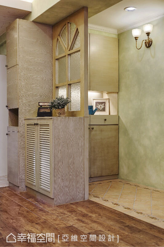 收納與圓拱窗構成的隔屏,與地面磁磚劃界出玄關段落,在充足機能之餘有了轉折的意義。