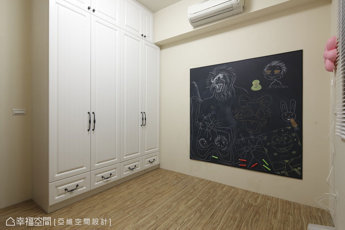 僅規劃當前也可使用的衣物收納機能,粉黃色調的預備次臥中,木作與黑板漆的運用成為家中寶貝天馬行空的塗鴉牆。