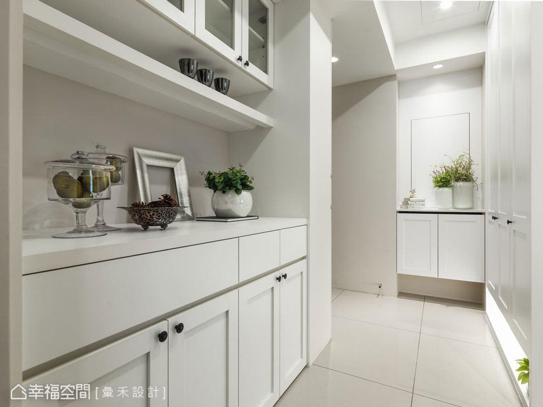 入門後純白色的烤漆櫃體不僅引領動線,也提供大量收納空間,而櫃體下方的燈光設計,則使視覺感受更輕盈。
