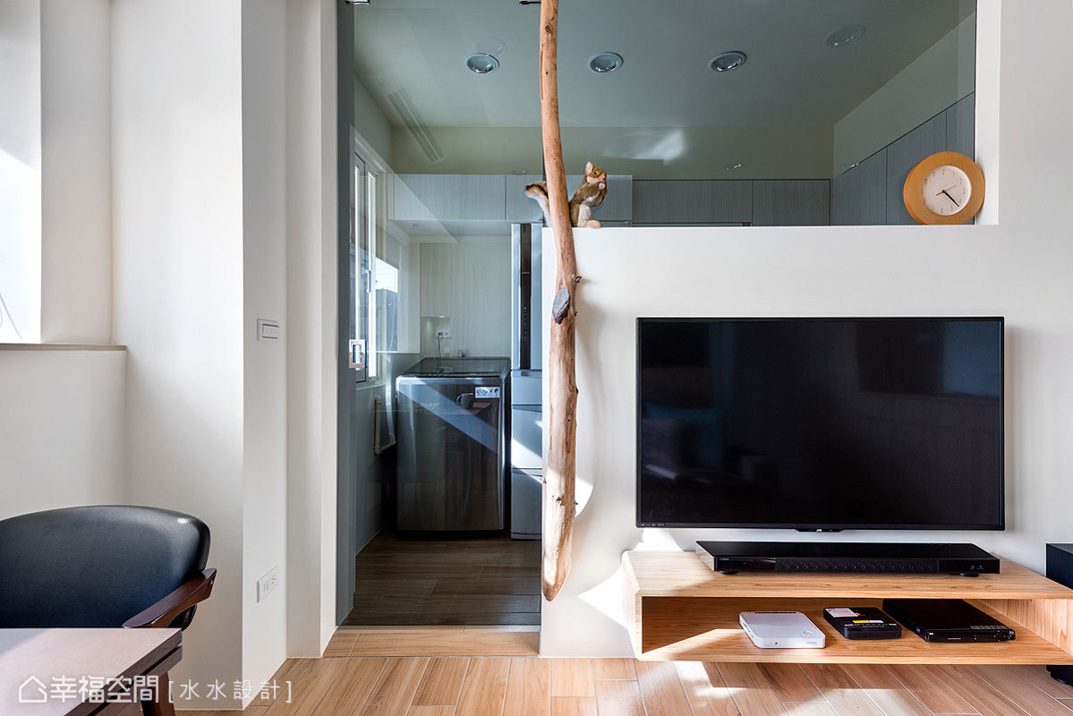 水水設計透過清透的灰玻與電視短牆,舒展空間的視覺尺度,並裝飾上一棵漂流木,輕鬆營造愜意無壓的氛圍。