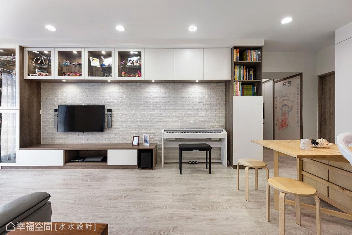 電視主牆鋪述溫暖調性的文化石,推演悠閒舒適的居家意象,上方並設置一排吊櫃,以玻璃及櫃面的方式,呈現收納及展示的多功能。