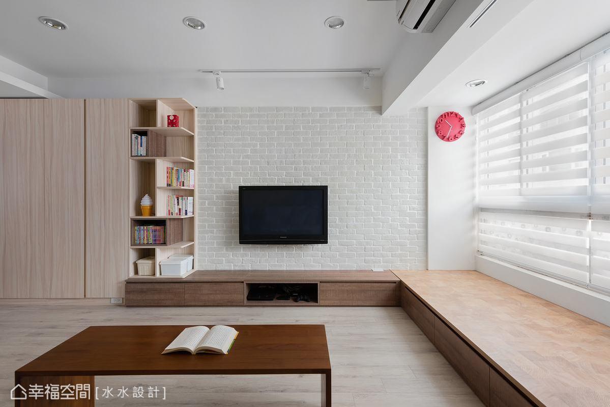 為滿足屋主年幼子女所需的活動空間,客廳拿掉多餘的傢俱裝飾,以木地板和臨窗臥榻提供舒適的聚享空間。