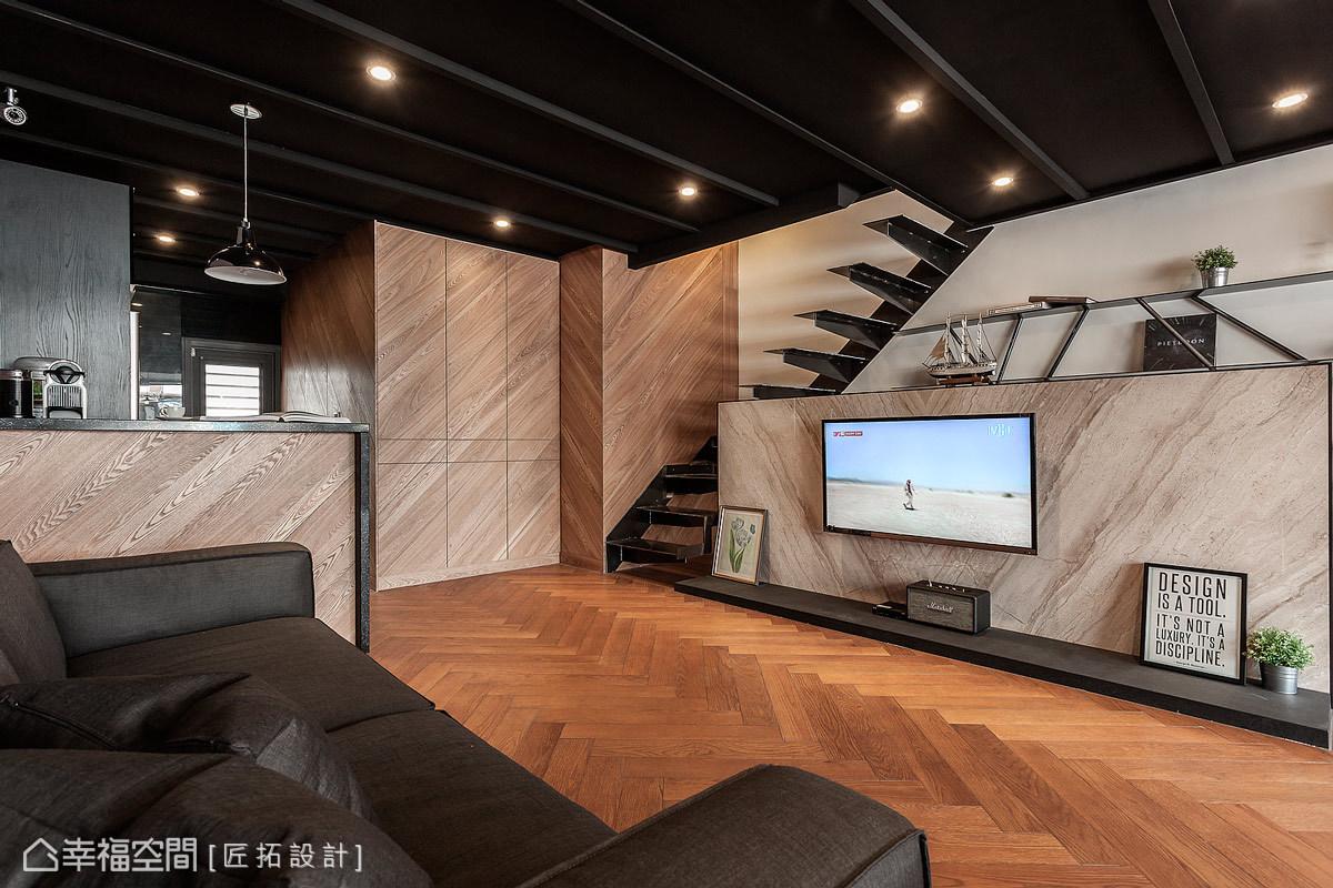 人字拼的地坪搭配斜貼的木皮立面,展現獨特的設計美感,也平衡了漆黑的樓梯與天花溫度。