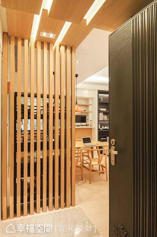 匠拓設計以一道木格柵屏風阻擋入門視線,化解風水疑慮,木紋語彙持續蔓延至天花板,創造整體一致的視覺性。