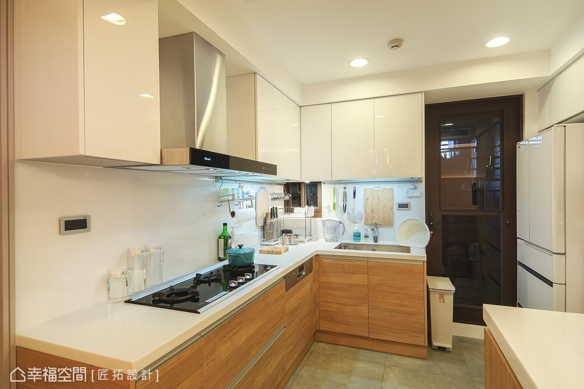 考量到清潔的便利性,選用人造石與水晶板材作為廚具檯面與吊櫃,並以木色做搭配,創造視覺的活潑感。