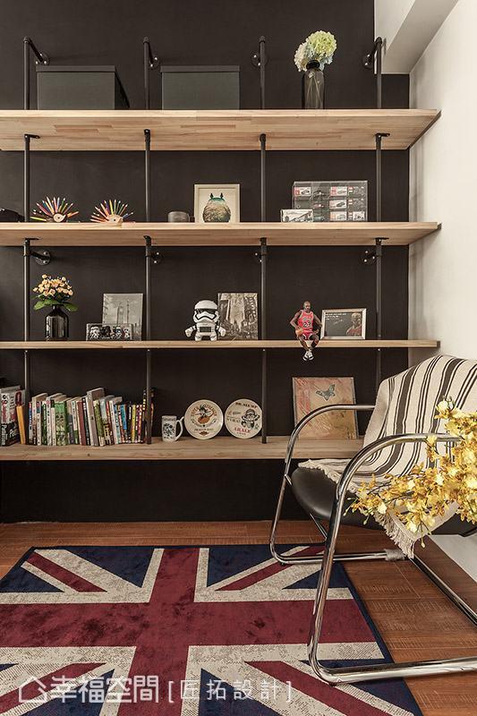 牆面利用深灰色飾底,搭配以原木拼接板與水管造型打造而成的開放展示櫃,簡單擺放書籍或是趣味小物,成為書房內質感別具的主題端景。