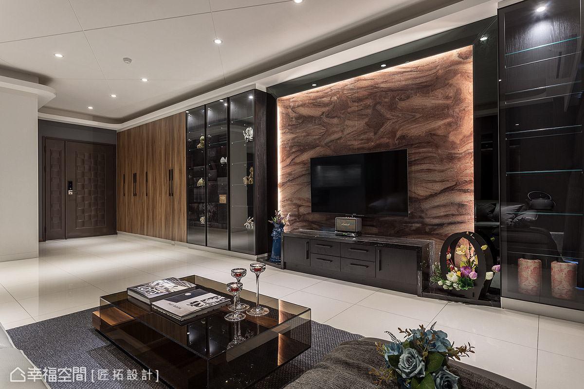 整面牆藉由櫃體材質與色彩予以整合,相近色調讓立面表情和諧一致,展示櫃特別搭配透明玻璃門,避免視覺過於壓迫。