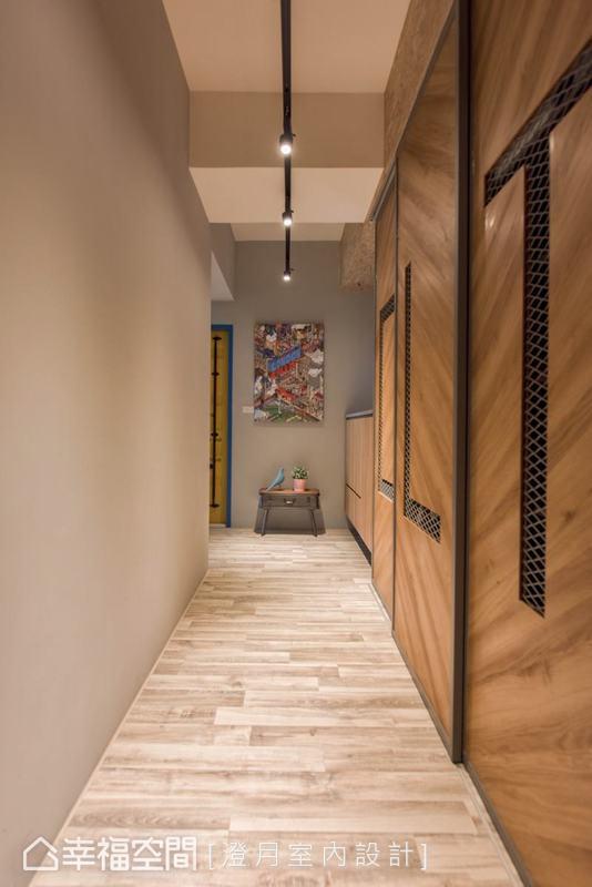 以大量的木質色系、清爽灰白色系、軌道燈與鐵件勾勒出玄關的清爽工業風格,玄關廊道底端則以屋主蒐藏的畫作營造充滿個人風采的空間端景。