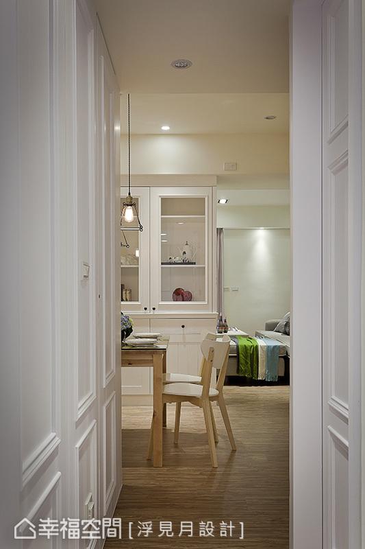 將開放式的餐廳設置於動線軸上,消弭原先狹長的走道深度,以白色壁板延展出和諧的立面造型,降低走道的壓迫感。