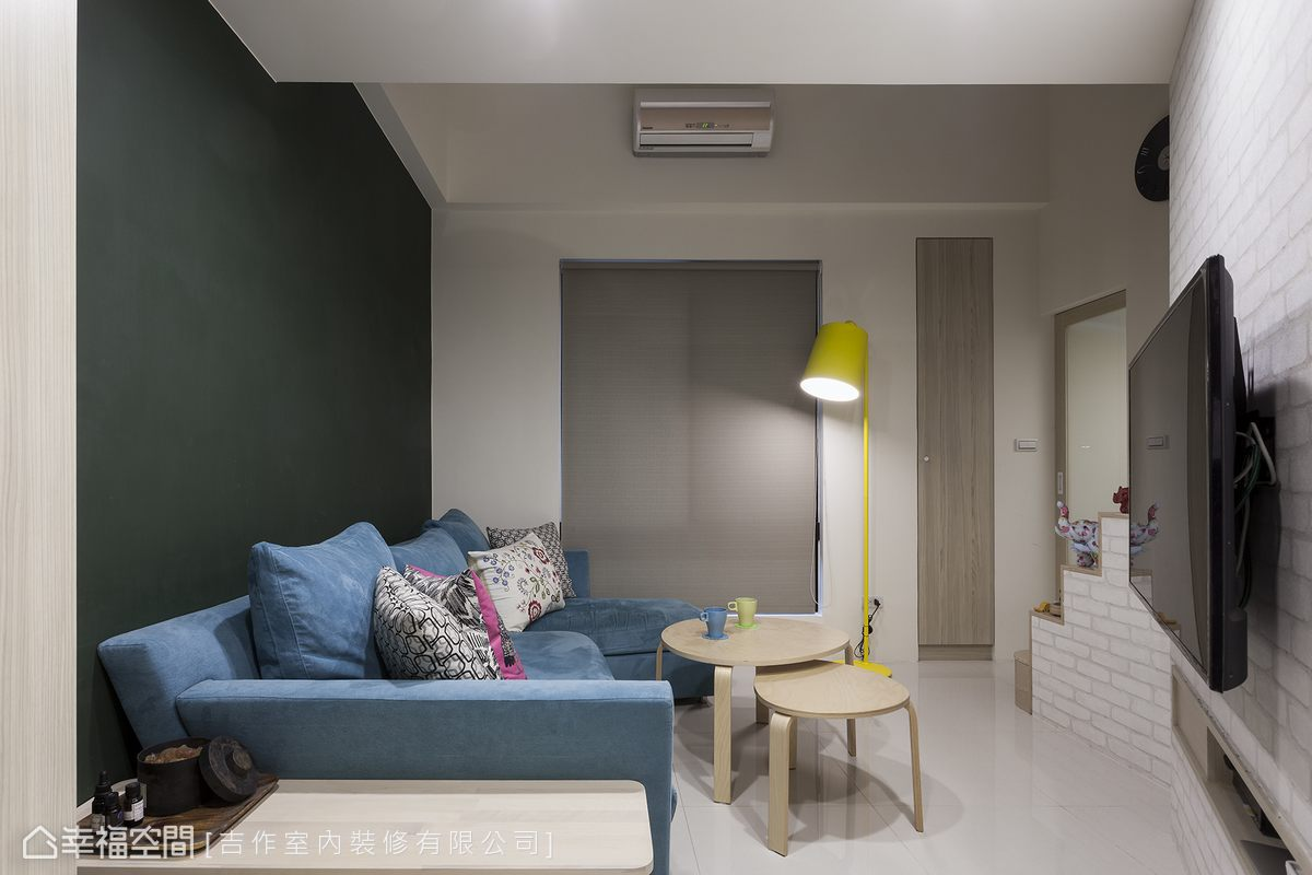沙發背牆的黑板綠來自屋主充分授權的大膽用色,創造出視覺景深的收縮感、有放大空間之效,同時托襯屋主喜愛的繽紛色調軟裝。