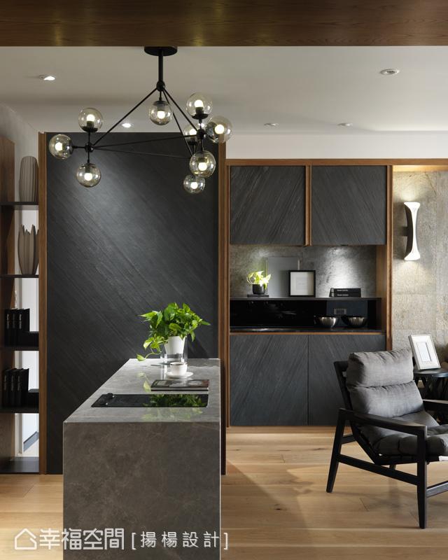 廚房與客廳間設置一道吧台劃分空間機能,而玄鐵黑的立面端景,搭配一盞饒富現代感的燈飾,為空間增添豐富神采。