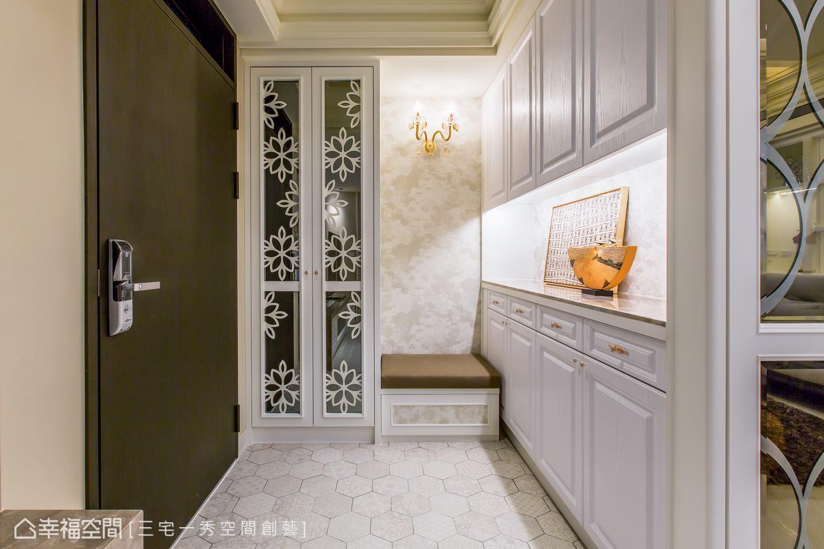 玄關衣帽櫃以黑鐵雷射切割,白色粉底烤漆及圖騰效果,帶出典雅的質韻,機能充足且放大空間感。並以優雅六角型地磚,搭配牆面壁紙,同樣增添雅緻的氛圍。