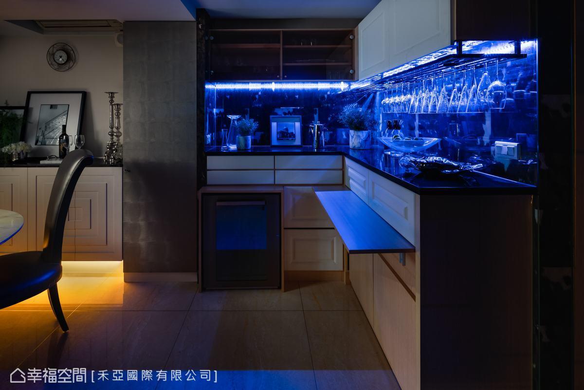 餐廚區設置L型吧台,上方是餐廚收納,下方為紅酒櫃,中間搭配藍色螢光LED燈,彷彿置身夜店,讓男主人能夠放鬆與好友暢飲。