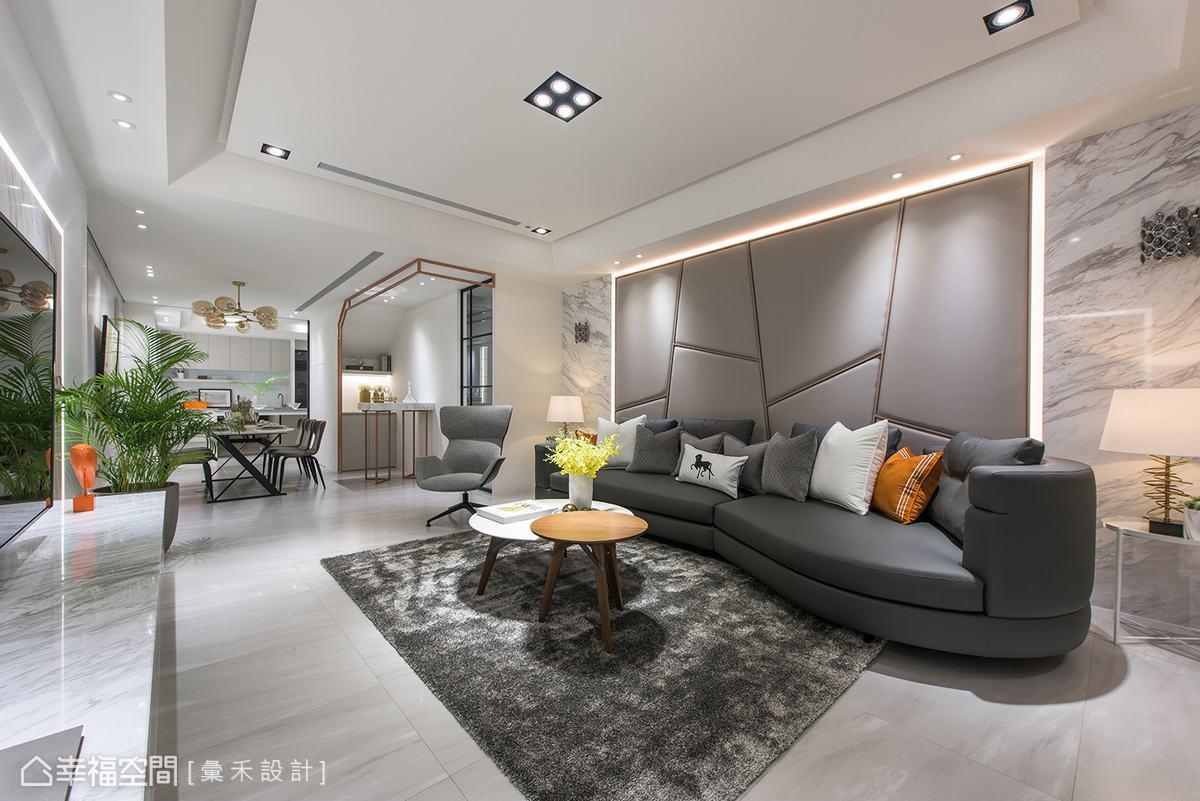 沙發背牆是淺灰色繃布的大區塊幾何造型,並以玫瑰金烤漆收邊,利用燈帶呈現金光熠熠的視覺變化。