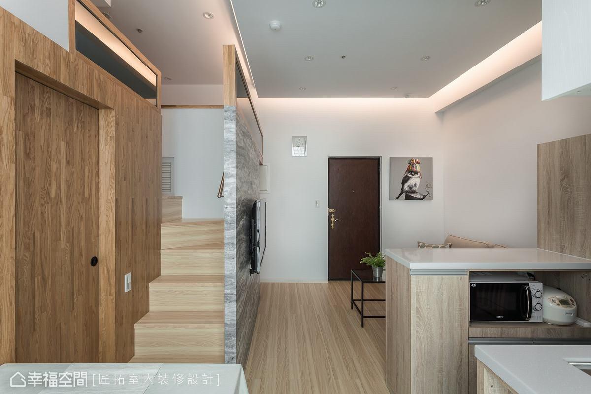 衛浴空間藏身在樓梯口旁,設計師以深色木皮劃分私領域的獨立性,對應公領域的淺色系,形成深淺交錯的層次感。