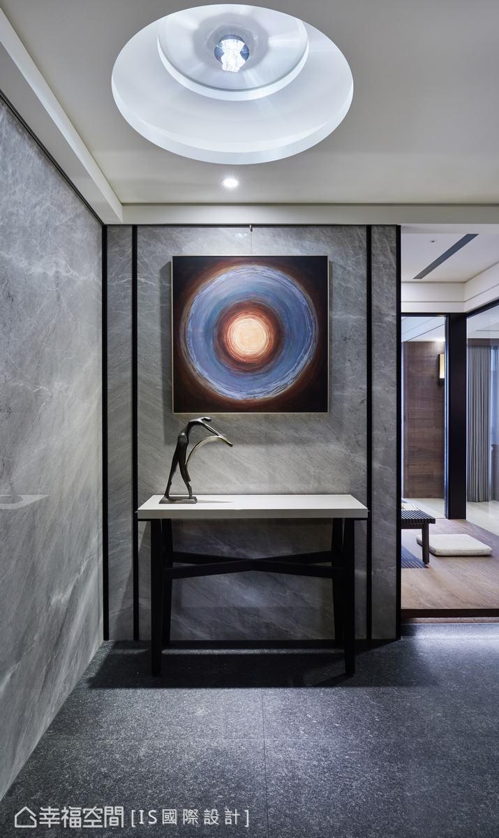 玄關入口運用石材順勢做出轉折,化身端景牆,勾勒精緻鐵件線,營造簡單俐落的視覺意象。