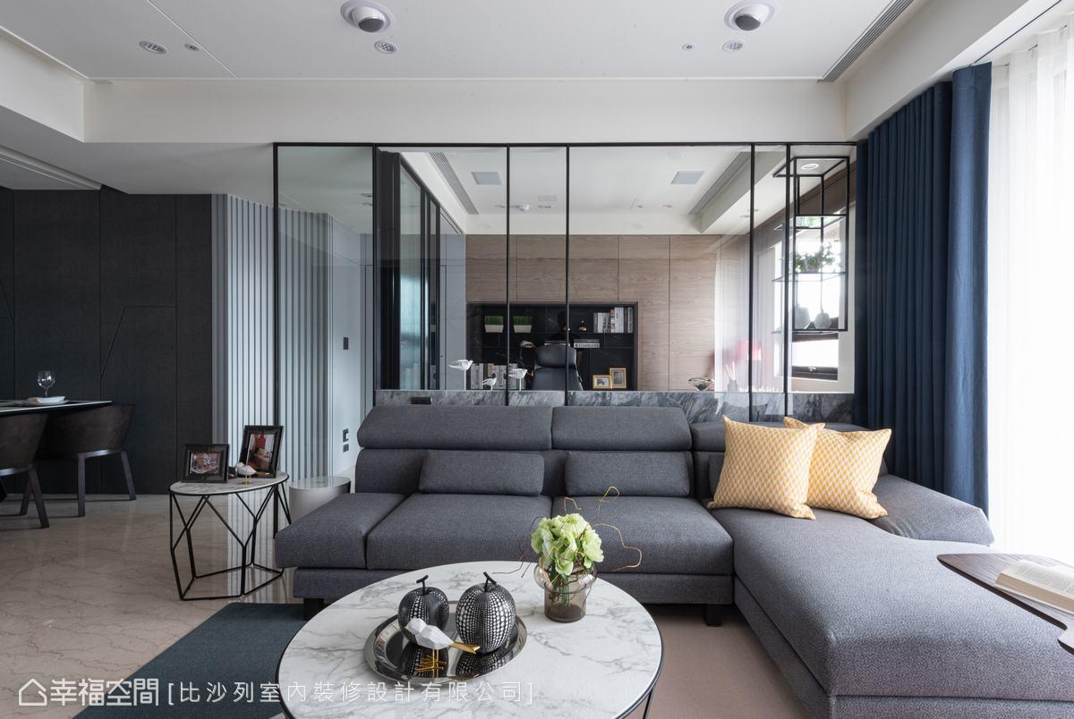 以清玻及鐵件區隔客廳與多功能室,打造穿透又深邃的視覺感受,灰色沙發軟件挹注靜謐氣息。