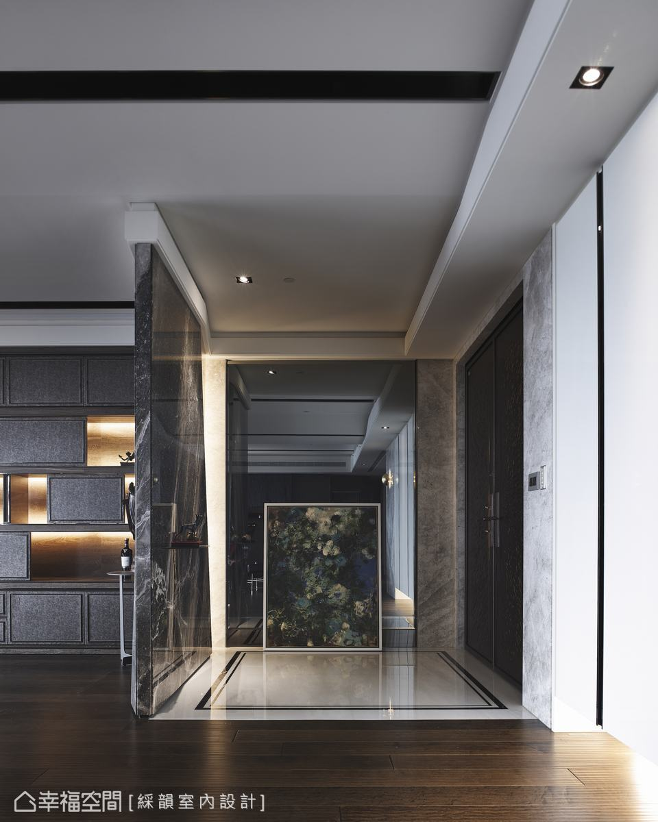 進門玄關端景石牆細藏巧思,鍍鈦金屬板規劃的展示檯面,透過折線斜角表現視覺引導的預告。