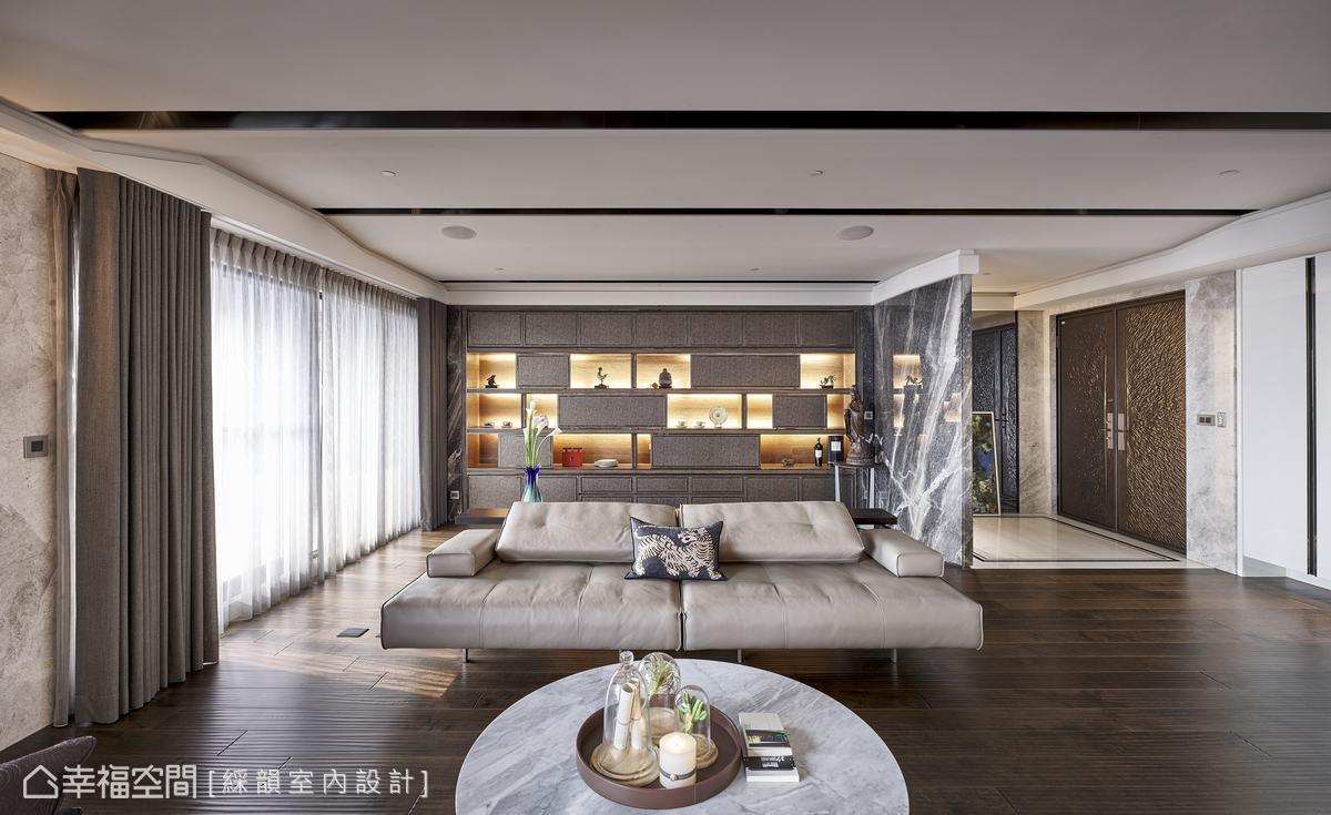 透過皮革與鍍鈦金屬規劃出沙發後方的展示牆,交錯開放與門片形式,滿足屋主擺放藝術品與收納CD需求,於內嵌燈光映照下,更成為客廳一大視覺焦點。