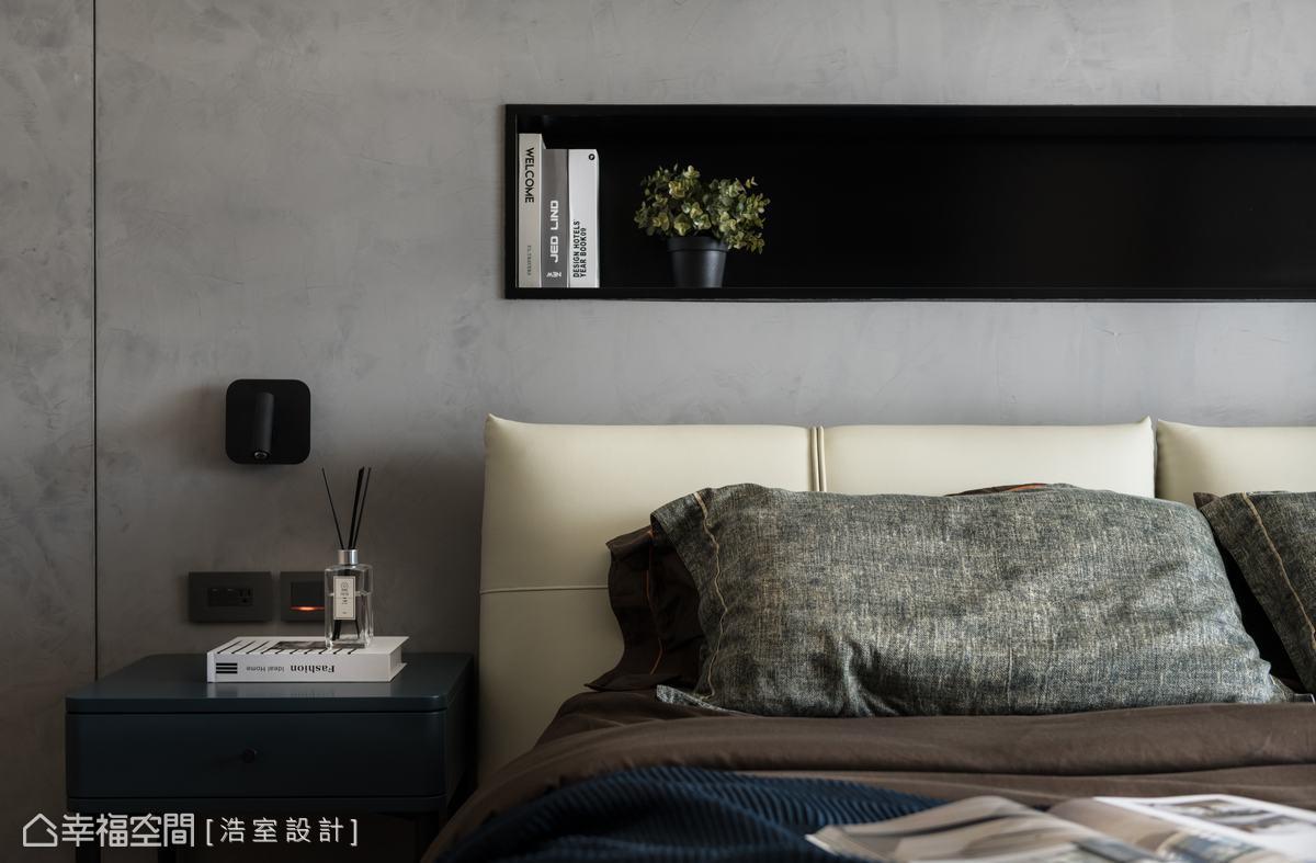 主臥室延續灰白空間調性之外,增加木皮的比例,賦予溫暖的寢臥質感。床頭背牆鋪敘灰色馬來漆,中間配置置物平台,方便使用又讓牆面有造型變化。