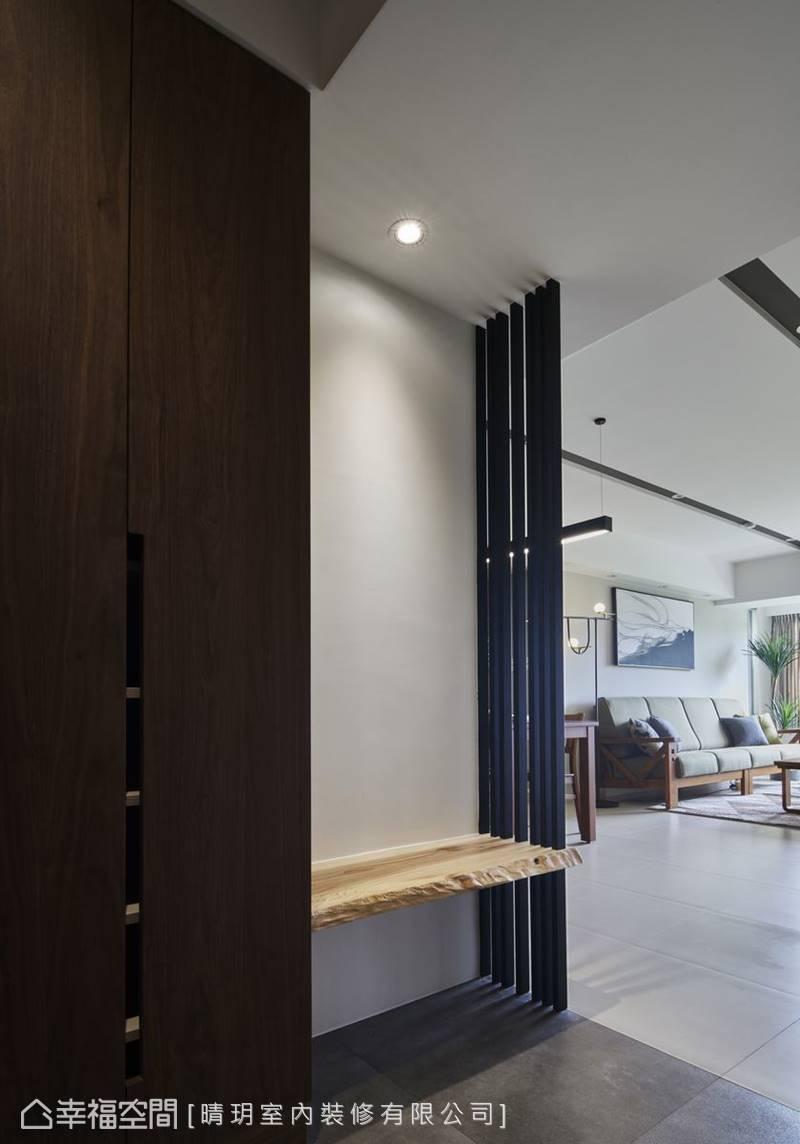 深色胡桃木木作櫃結合原木穿鞋椅、鐵件格柵的設計,散發質樸幽靜美感。