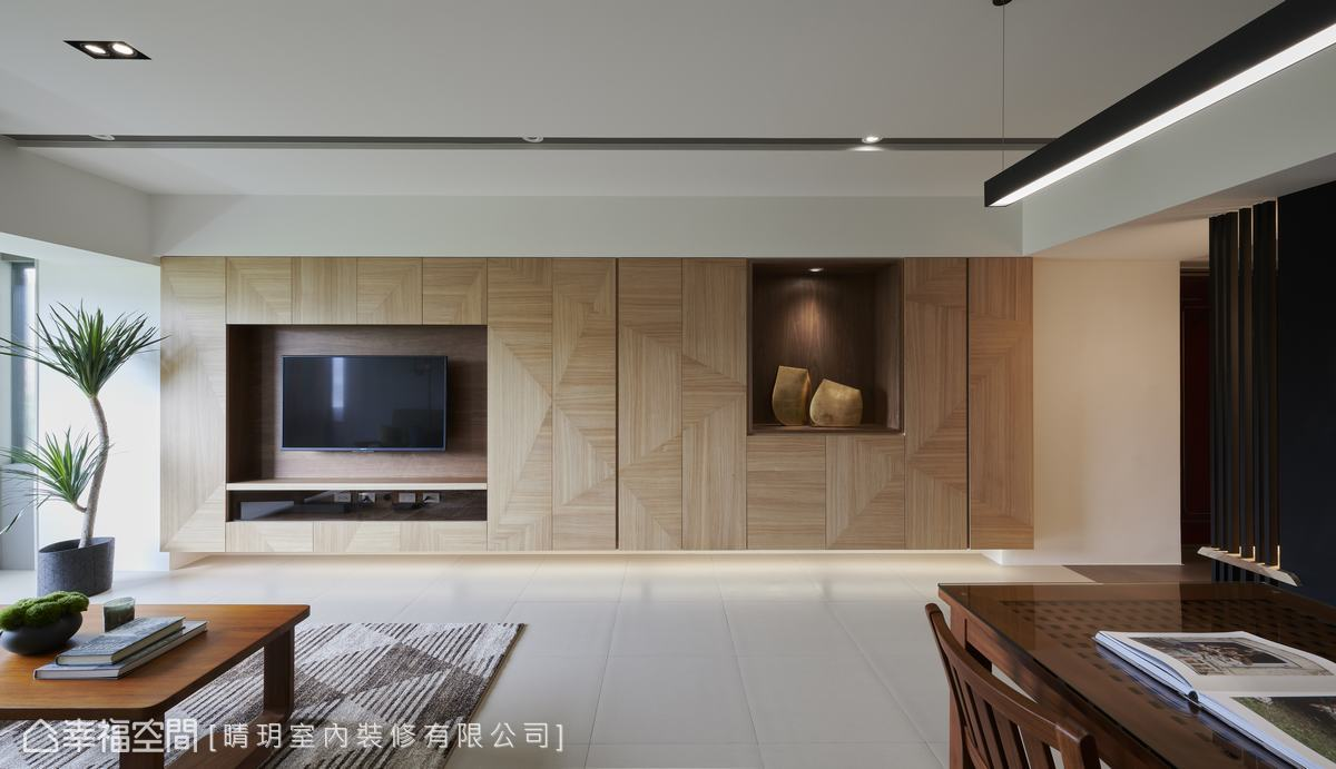 客廳電視主牆幾何拼花木質在柔和天光漫射下,隱約顯現放射狀肌理,宛若楓葉脈絡由中心舒展而開的姿態。
