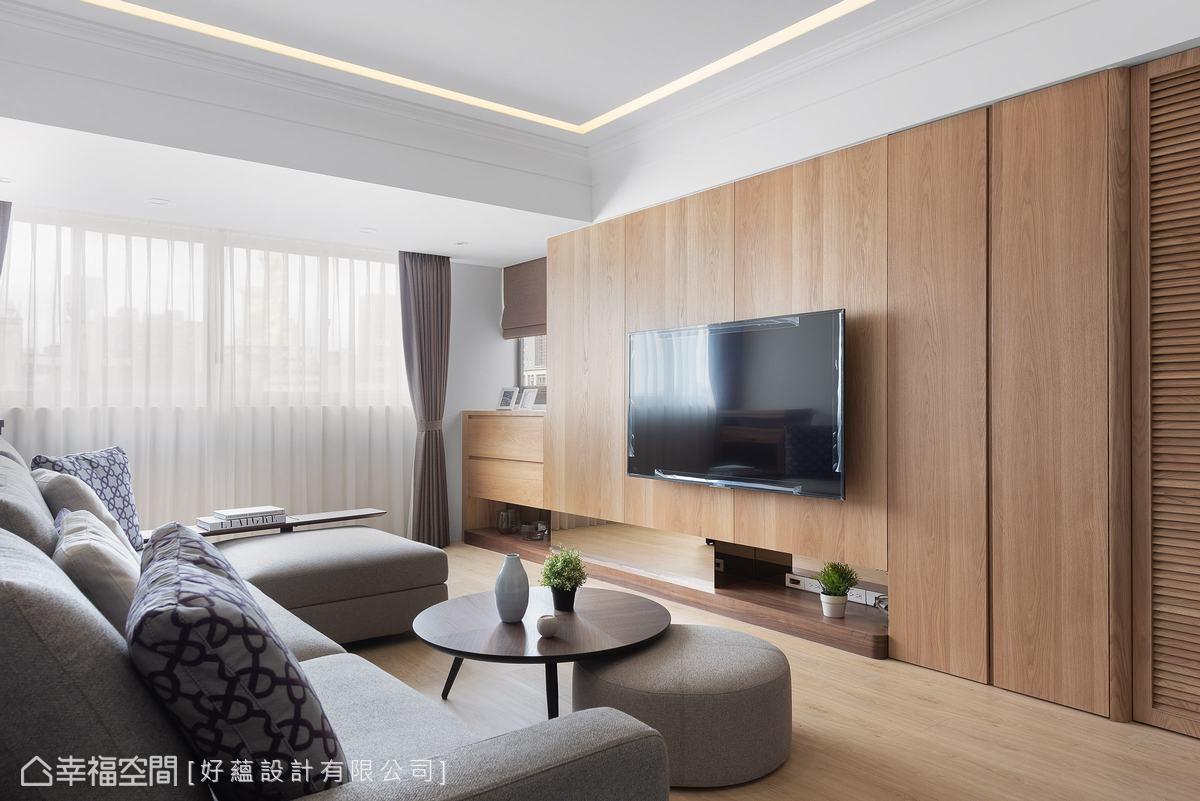 利用樑下空間規劃鞋櫃收納及電視牆,一氣呵成的木元素,搭配下方鏤空留白與鏡面,延伸場域深度。